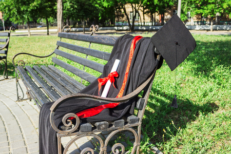 Graduation cap, hat with black tassel, mantle with a degree of paper on a park bench