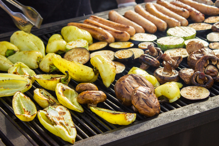 carnes y verduras: Assorted delicious grilled meats with vegetables over the barbecue on the charcoal. Sausages, steak, pepper, mushrooms, zucchini. Foto de archivo