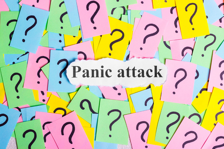 paper sheet: Panic Attack Syndrome text on colorful sticky notes Against the background of question marks Stock Photo