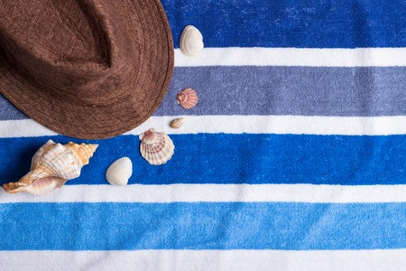 A summer holiday composition on a beach towel with seashells and a hat. Stock Photo