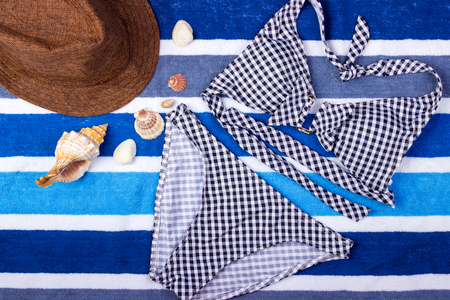 swimsuit with beach accessories on blue background