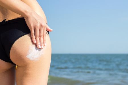 girl applying suntan lotion on her buttocks at the beach