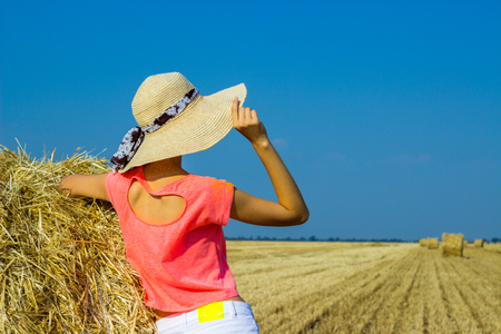 haymow: Sexy woman on hay stack on sunset. Beauty romantic girl outdoors against hay stack. Photo of sexy girl in a field with haystacks