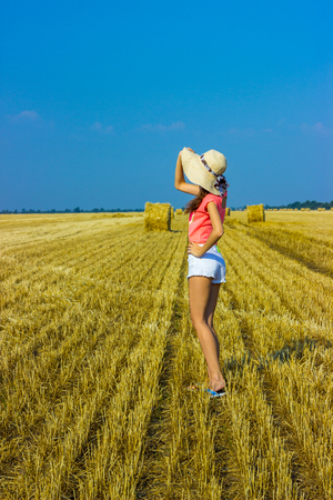 Happy woman on hay stack in sunny day. Beauty romantic girl outdoors against hay stack Stock Photo