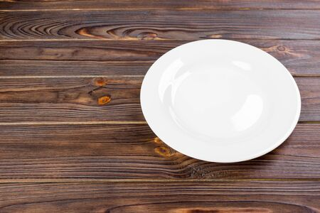 Empty white plate on wooden table top view.