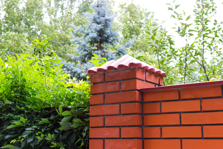 Corner of the brick fence of a country house Stock Photo