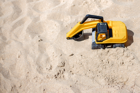 industrail: The excavator toy on the beach working with sand. industrail symbols