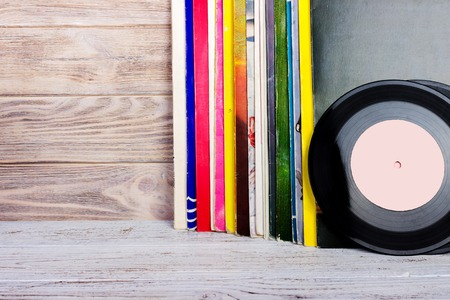 lps: Retro styled image of a collection of old vinyl record lps with sleeves on a wooden background. Copy space. Stock Photo
