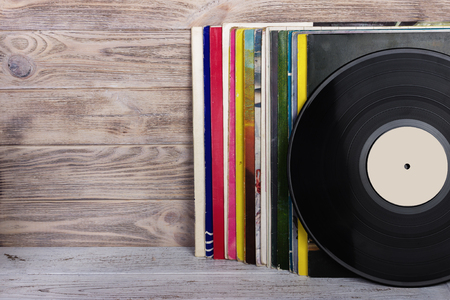 Retro styled image of a collection of old vinyl record lps with sleeves on a wooden background. Copy space. Stock Photo