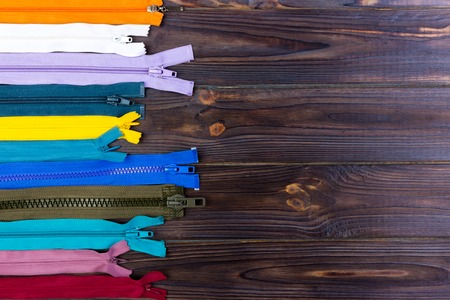 Multicolored zippers are laid out on a wooden table Stock Photo