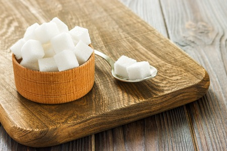 Bowl and spoon full of sugar on wooden background Stock Photo