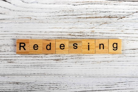 REDESIGN word made with wooden blocks concept Stock Photo