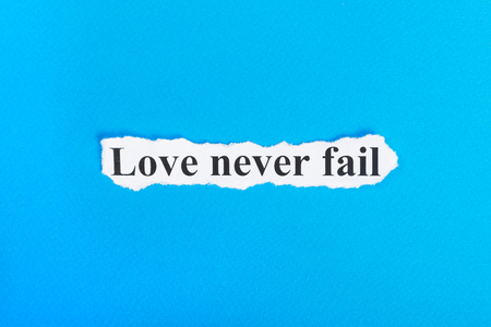 Love never fail text on paper. Word Love never fail on torn paper. Concept Image. Stock Photo