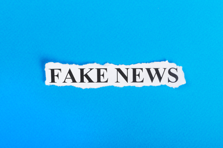 FAKE NEWS text on paper. Word FAKE NEWS on torn paper. Concept Image. Stock Photo