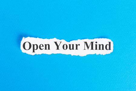 OPEN YOUR MIND text on paper. Word OPEN YOUR MIND on torn paper. Concept Image. Stock Photo