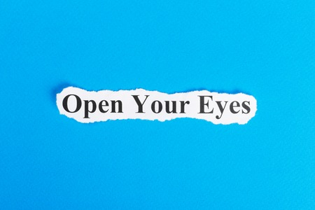 Open Your Eyes text on paper. Word Open Your Eyes on torn paper. Concept Image. Stock Photo
