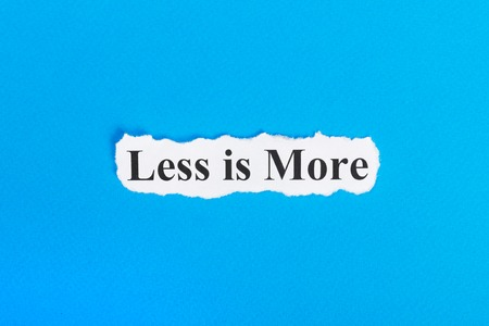 work less: less is more text on paper. Word less is more on torn paper. Concept Image.