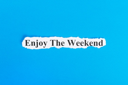 enjoy the weekend text on paper. Word enjoy the weekend on torn paper. Concept Image. Stock Photo
