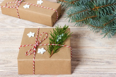 Christmas or New Year presents wrapped in natural colored paper and decorated with traditional Xmas twine and fir twigs on white background. Stock Photo