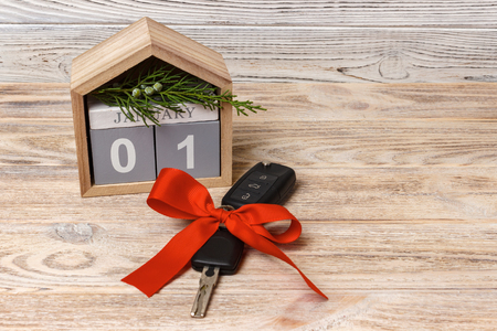 Close-up view of car keys with red bow as present and calendar on wooden background on wooden background.