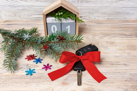 Car key with colorful bow and calendar, christmas tree, branches, snowflakes, on wooden background.