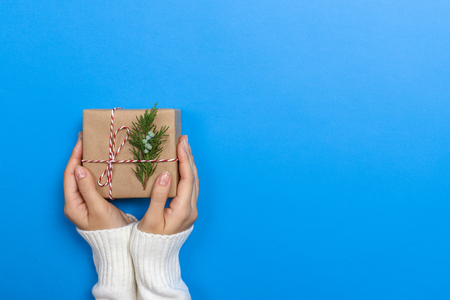 Woman hands holding a Christmas gift box. Christmas presents and New Year. Handmade. Stock Photo
