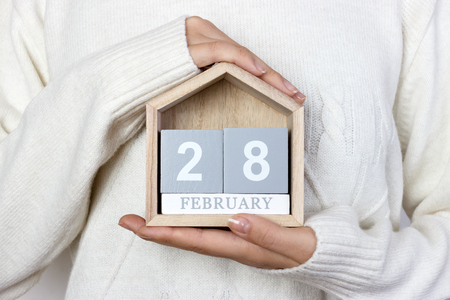 February 28 in the calendar. the girl is holding a wooden calendar. Rare Disease Day, Shrove Tuesday, International Pancake Day.