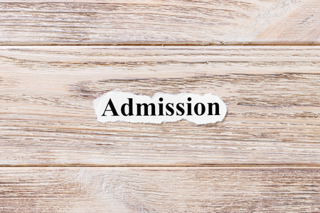 ADMISSIONS of the word on paper. concept. Words of ADMISSIONS on a wooden background.