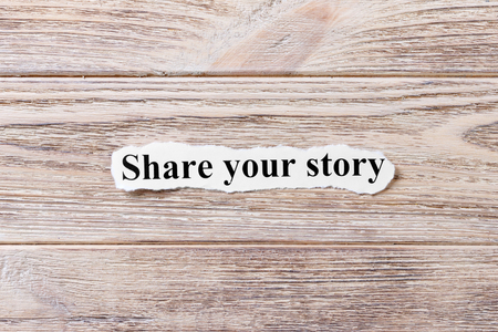 Share your story of the word on paper. concept. Words of Share your story on a wooden background.