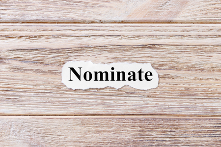 NOMINATE of the word on paper. concept. Words of NOMINATE on a wooden background. Stock Photo