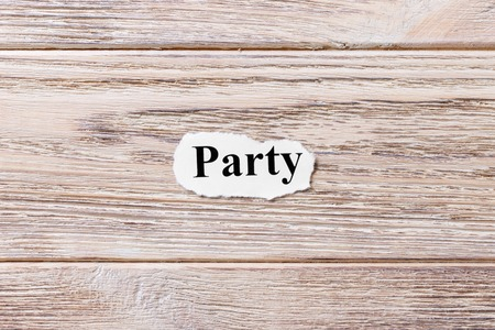 PARTY of the word on paper. concept. Words of PARTY on a wooden background.