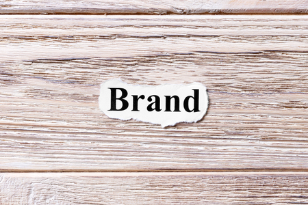 BRAND of the word on paper. concept. Words of BRAND on a wooden background.