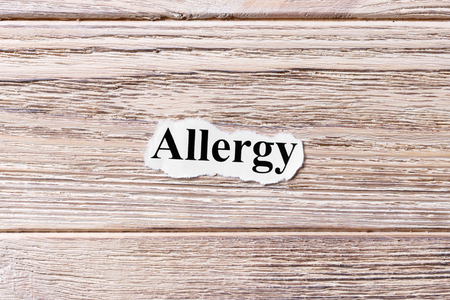 Allergy of the word on paper. concept. Words of Allergy on a wooden background.