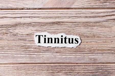 Tinnitus of the word on paper. concept. Words of Tinnitus on a wooden background.