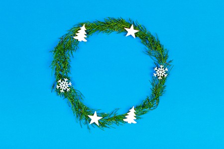 christmas or new year composition. christmas round frame made of winter decoration on blue background with copy space for text. holiday and celebration concept. flat lay. top view.