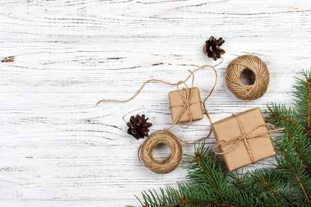 Christmas decoration elements: string, chrtistmas tree branches with cones and several decorated gifts on white wooden background.