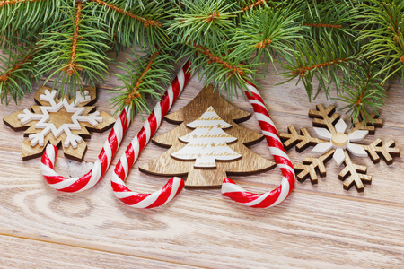 Christmas candy canes and snowflakes on a wooden background.