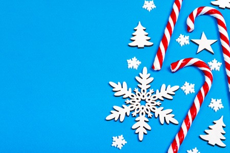 Christmas candy cane lied evenly in row on blue background with decorative snowflake and star. Flat lay and top view.
