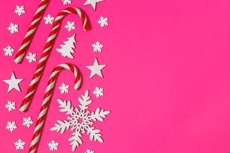 Christmas candy cane lied evenly in row on pink background with decorative snowflake and star. Flat lay and top view. Stock Photo
