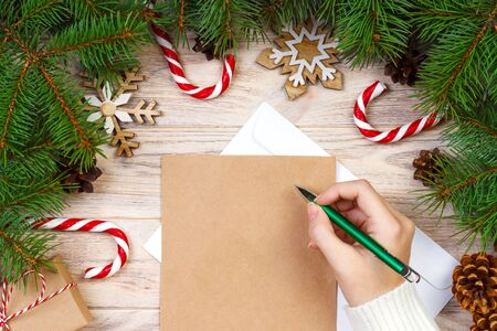 girl hand writing christmas letter on craft paper with decorations on wooden background stock photo - Christmas Letter Decorations