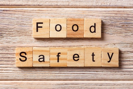 Food safety word written on wood block. Food safety text on table, concept.
