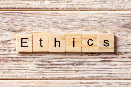Ethics word written on wood block. Ethics text on table, concept.