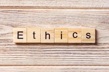 나무 블록에 작성 된 윤리 단어입니다. 테이블, 개념에 윤리 텍스트입니다.