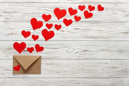 Hearts fly out from the envelope. Love Letter. Background Valentine Day on wooden background. Stock Photo