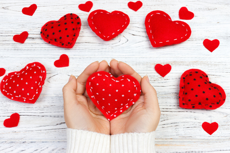 Female hands giving red heart. Valentine day background.