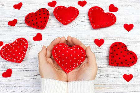 Vrouwelijke handen die rood hart geven. Valentine dag achtergrond.