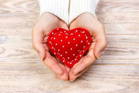 A woman holds a red heart in her hands. Love concept.