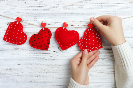 girl hanging hearts on a rope. wooden background.
