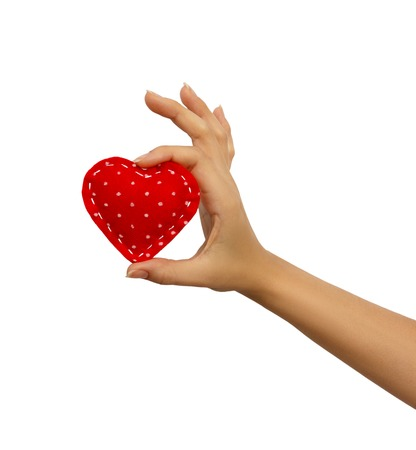 Hand holding a red heart isolated on white background. Stock Photo