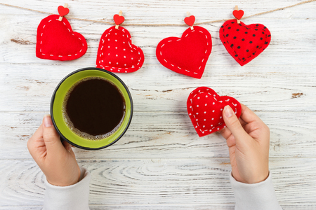 Above view of female hand holding hot cup of coffee with red heart on wood table. Photo in vintage color image style.